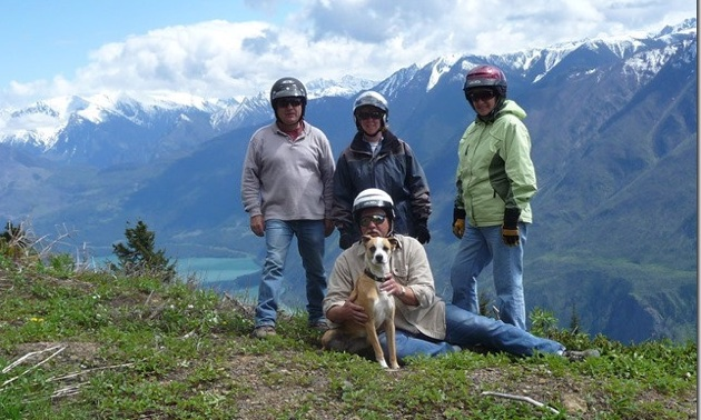 Phil and Delle Megyesi,  Tom and Beryl Maxwell and Phil's dog cooper are posing on a hill with snowcovered mountains in the background.