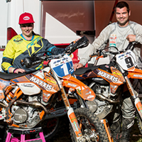 Chantelle Bykerk and Bobby Prochnau, endurocross racers standing by their bikes.