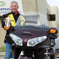 A grey haired man holding a message in a bottle and standing by a purple Honda Goldwing.