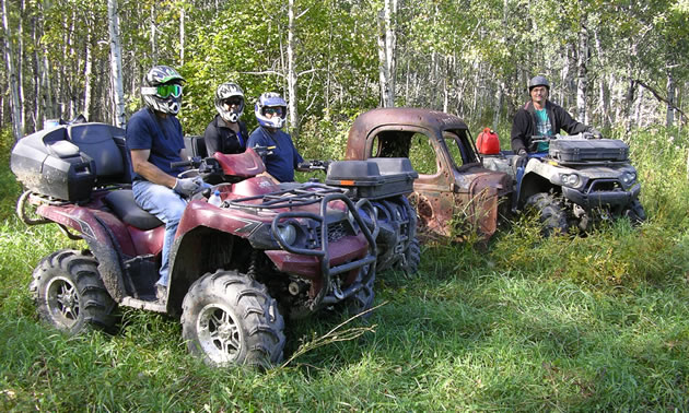 Several people pose on their muddy ATV's for a picture.