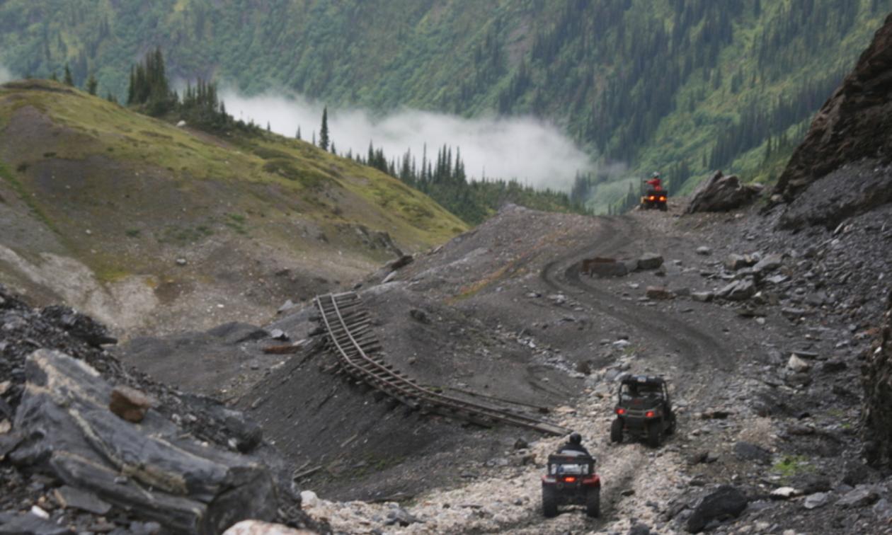 A few ATVers ride a trail near railroad tracks.