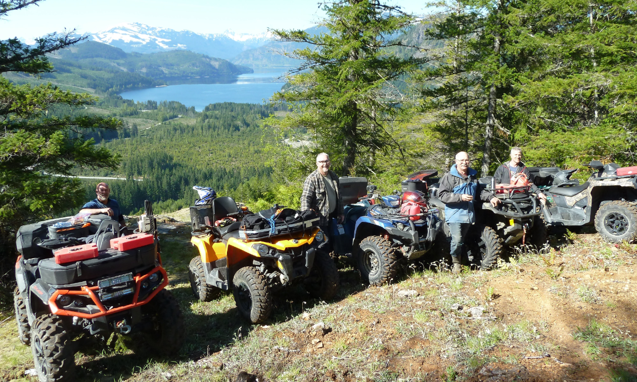 A lineup of ATVers standing next to their ATVs on the side of a mountain.