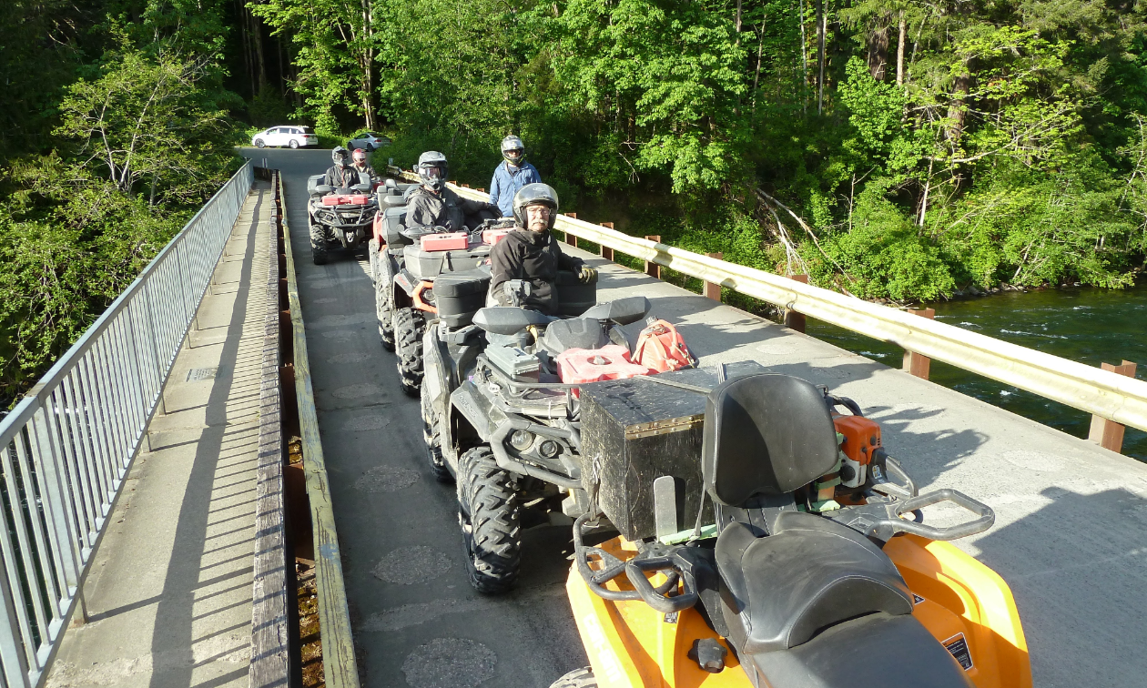 A bridge filled with ATVs in the woods.