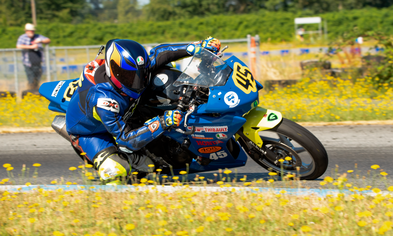 Andrew Van Winkle leans into a tight turn on his blue Honda CBR250R motorcycle on a race track.