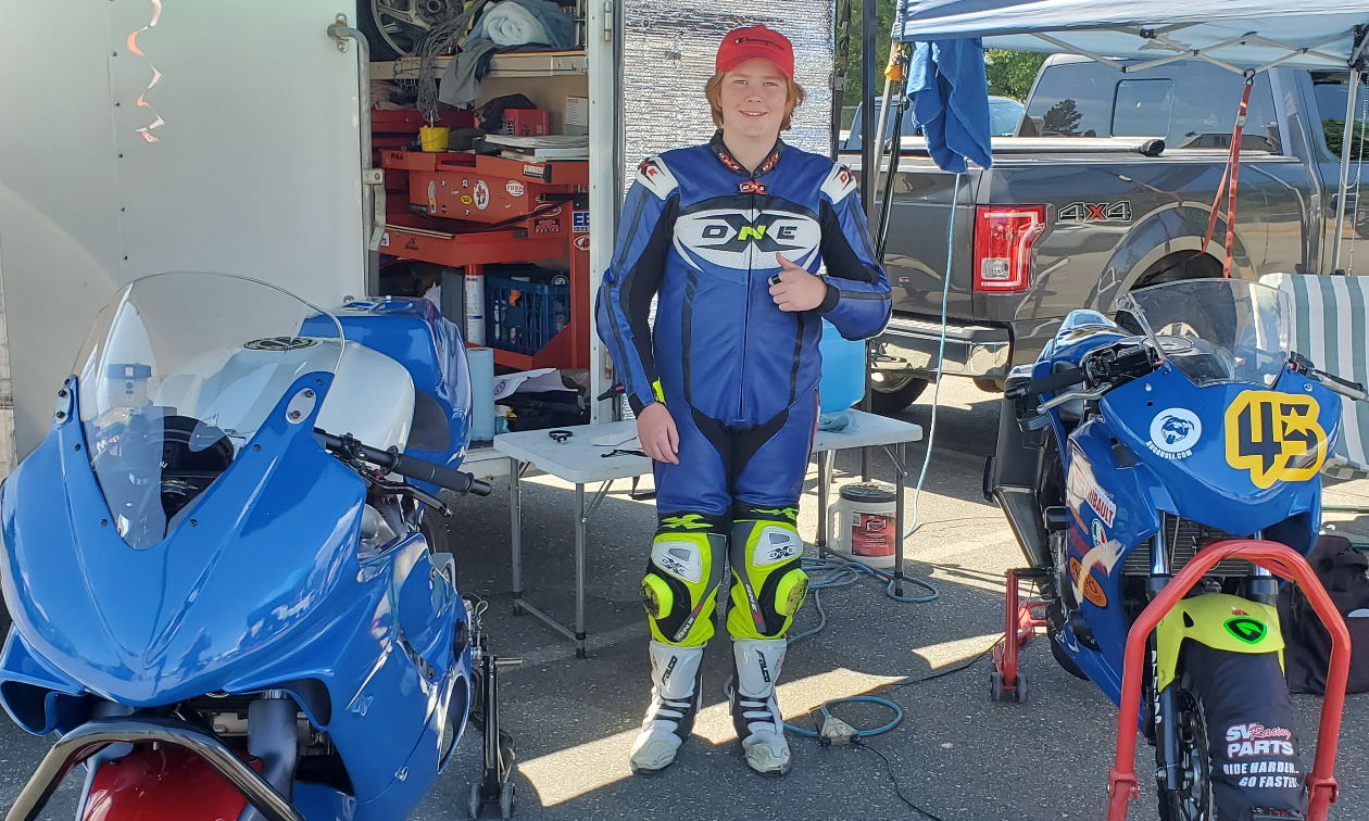 Andrew Van Winkle smiles while standing next to his blue Honda CBR250R under a tent in a parking lot.
