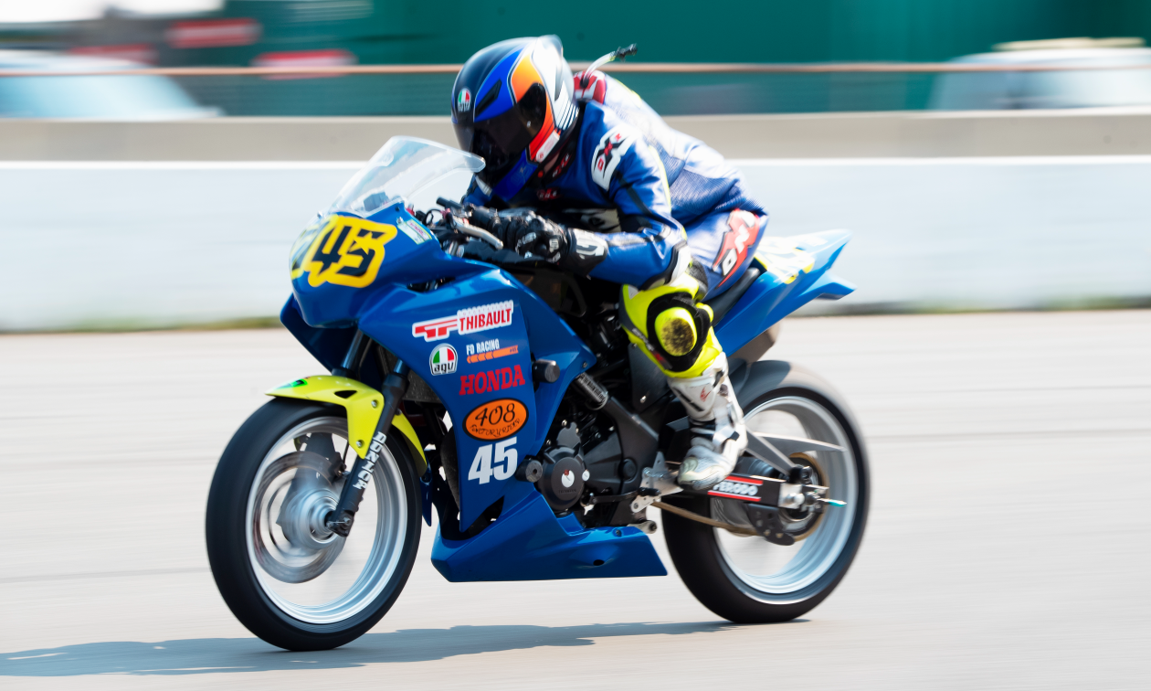Andrew Van Winkle rides a blue Honda CBR250R motorcycle at high speeds on a race track.