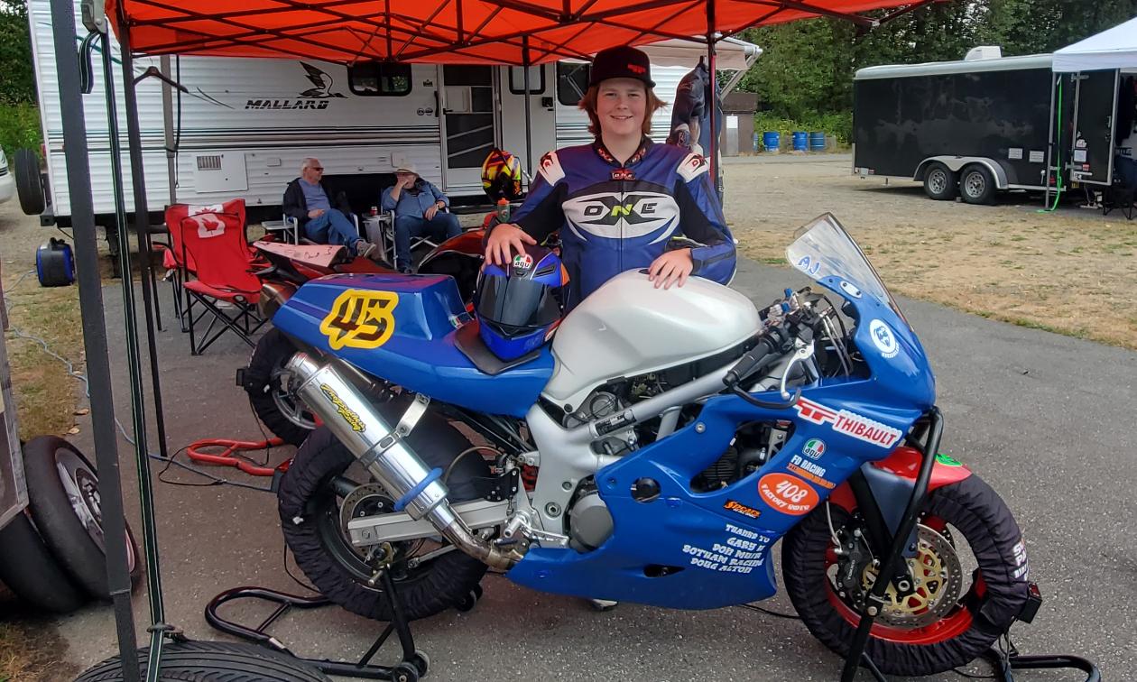 Andrew Van Winkle poses behind his motorcycle underneath a red tent.