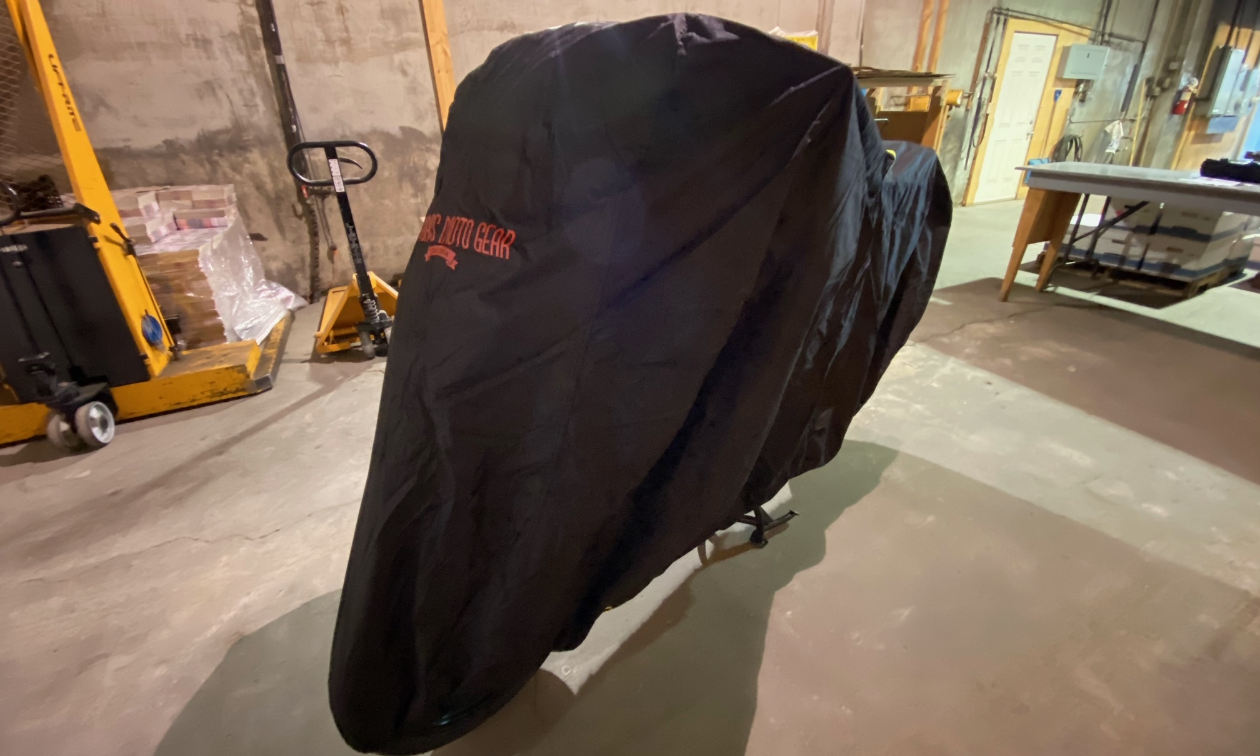 A black Badass Moto Ultimate All Wx Waterproof Motorcycle Cover covers a motorcycle in a garage.