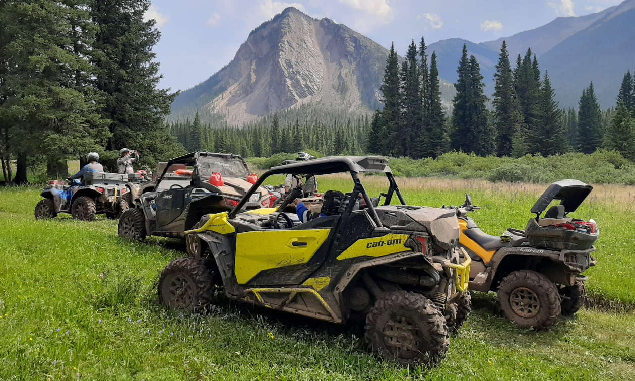 Four side-by-side ATVs are parked in a glade while a mountain juts out of the ground in the distance.