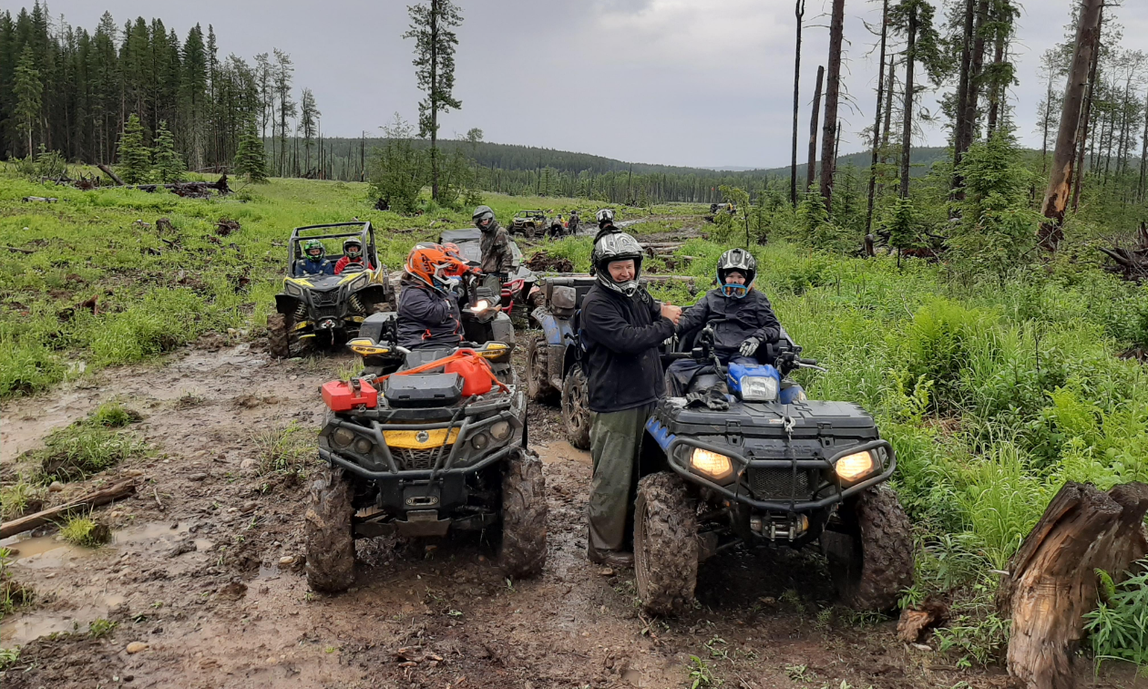 Several ATVs are parked on a muddy road in a wooded area.