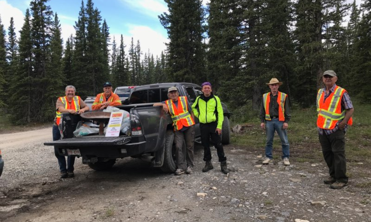 Six men stand near a truck on a gravel road wearing reflective jackets.