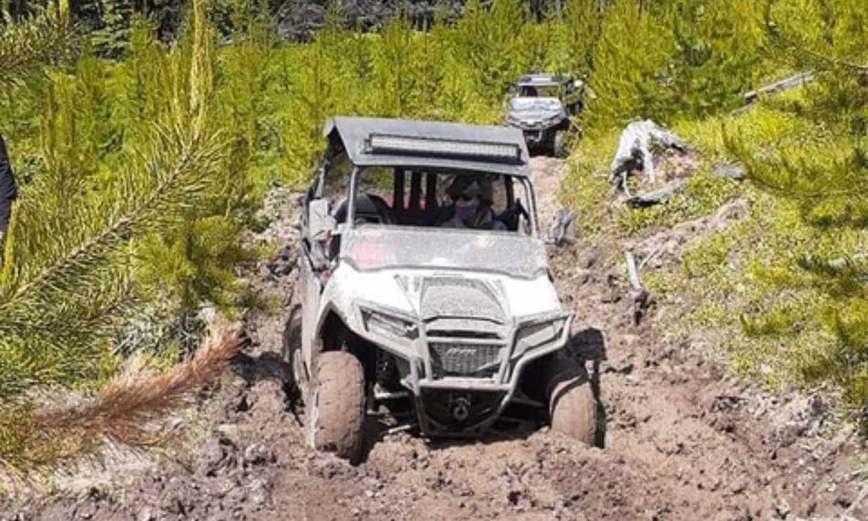 A side-by-side ATV plows through a muddy dirt road.
