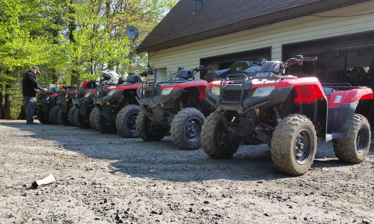 Five red ATVs are in a row in front of a garage.