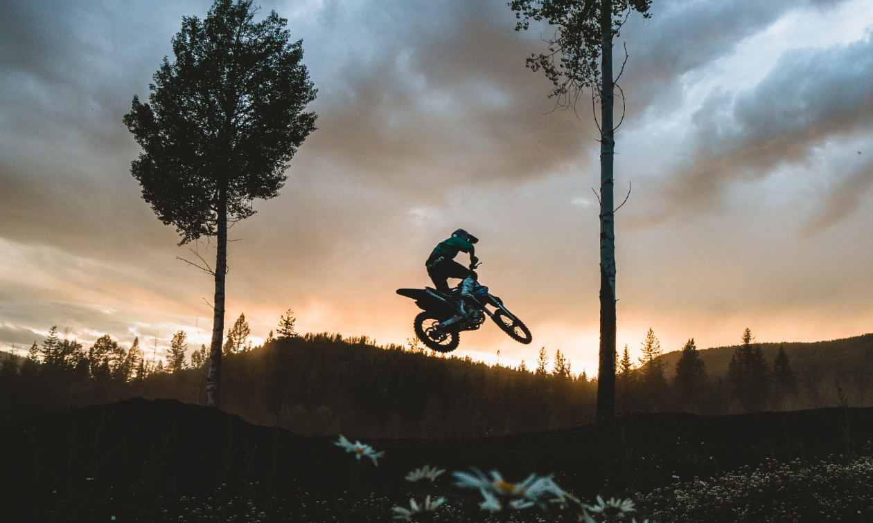A dirt bike rider gets big air off a jump on the Kootenay Motocross track at sunset.