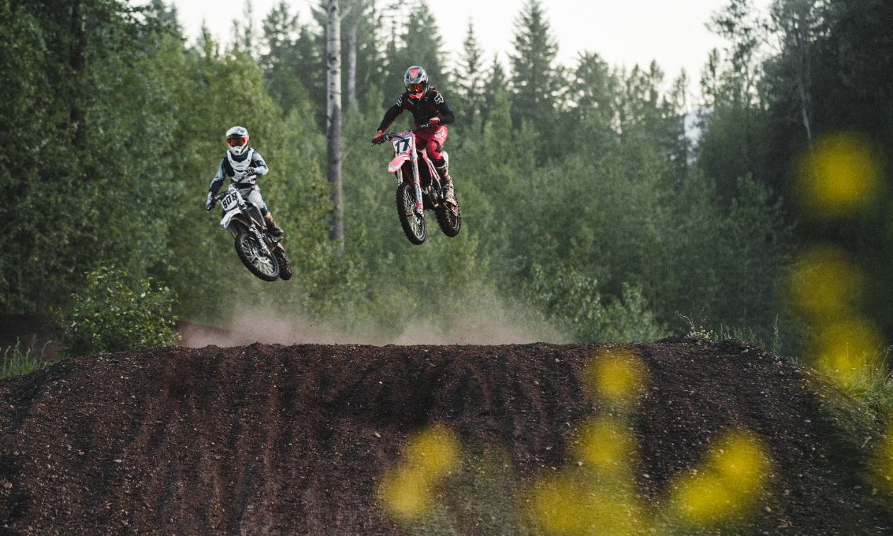 Two dirt bikers get big air off of a jump on the West Kootenay Recreational Dirt Bike and ATV Society motocross track.