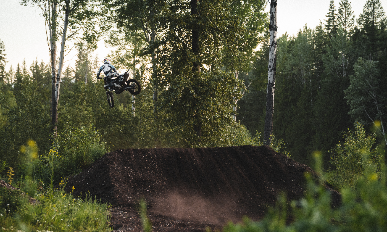 A dirt biker does a jump at the West Kootenay Recreational Dirt Bike and ATV Society motocross track.