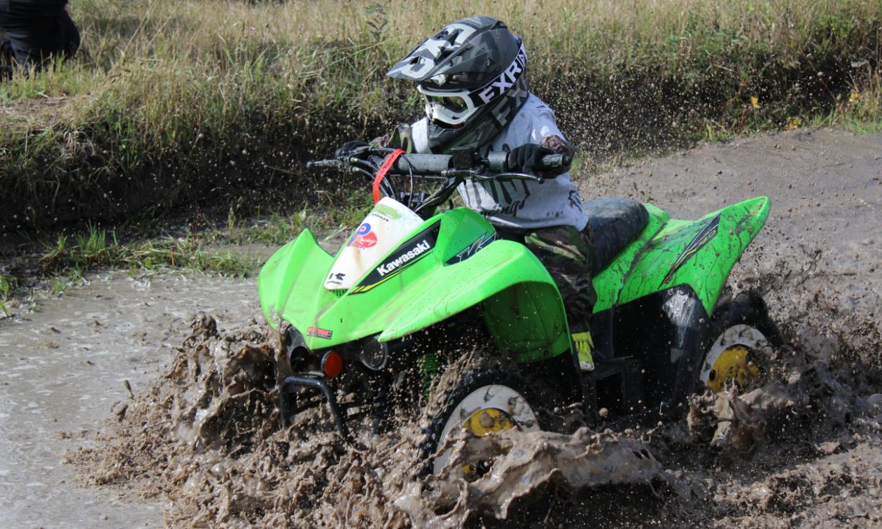 Eason Hawthorn rides a green Kawasaki KFX 50.