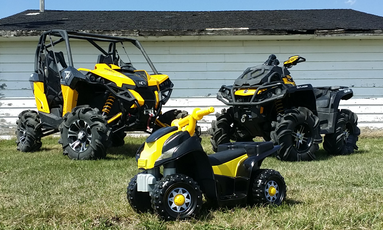 ATVs Maverick and 650 XMR behind a small battery-powered quad with a custom paint job to match the Can-Am black and yellow.