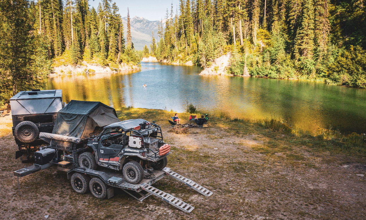 A river in Montana. On the near shoreline, a Dodge Ram 3500, carrying a Patriot Camper TH610 trailer with a Polaris General 1000.