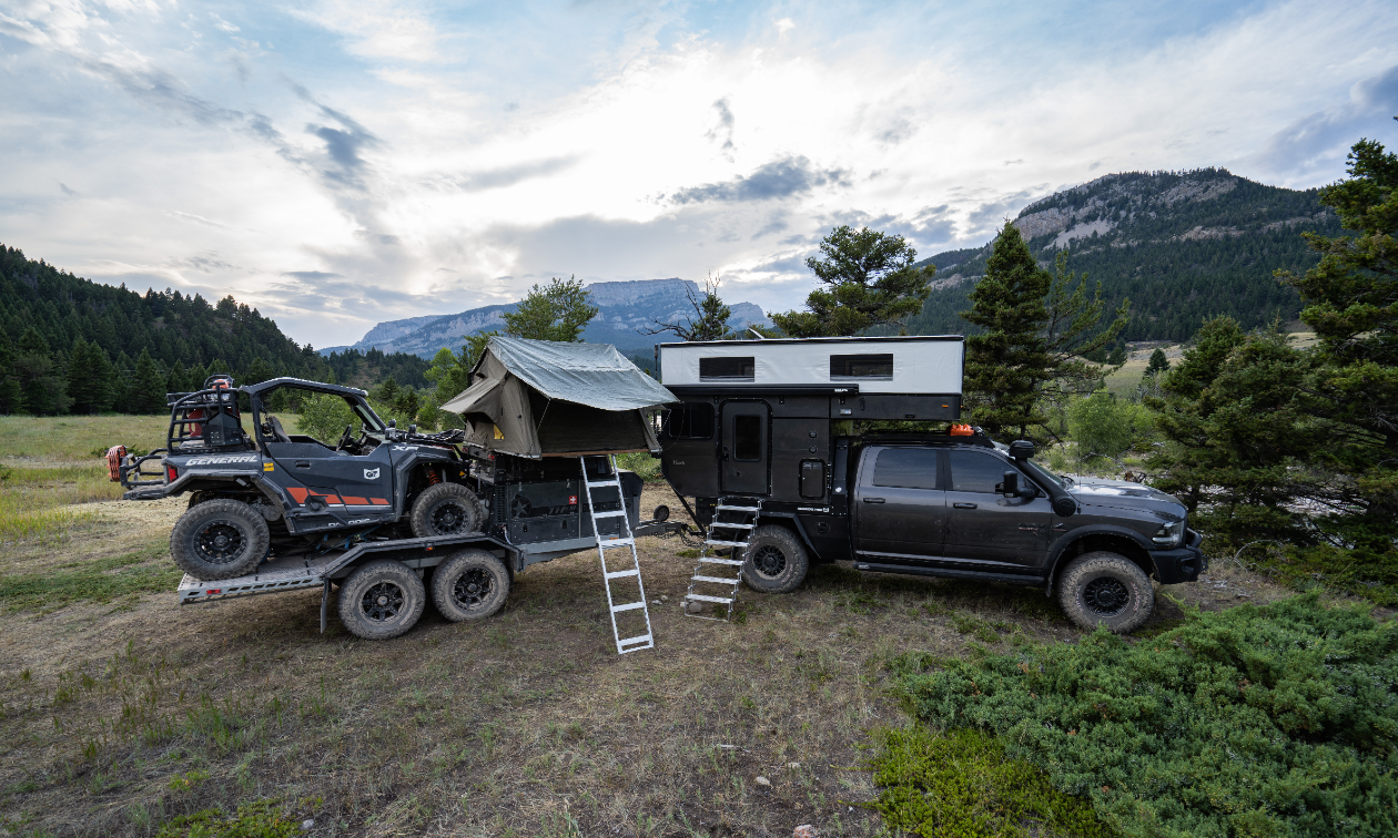 In a glade in Montana, a Dodge Ram 3500, carrying a Patriot Camper TH610 trailer with a Polaris General 1000.