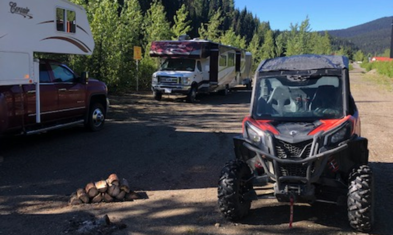 An ATV is parked next to two RVs on a dirt road lined with trees on one side and a field on the other side.