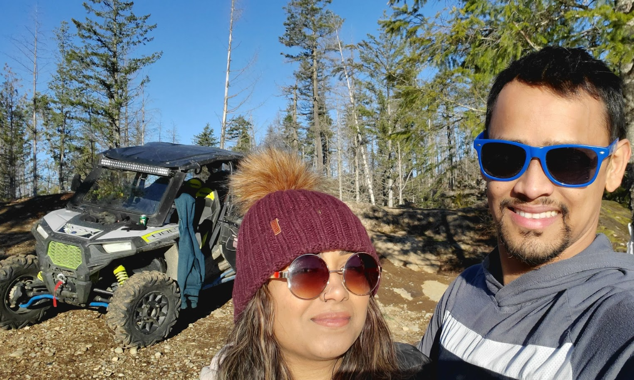 Melvin Garib and his wife pose for a photo with sunglasses on and a RZR side-by-side behind them.