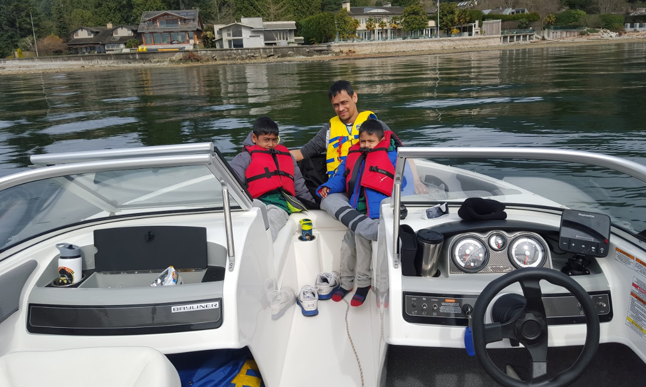 Melvin Garib sits next to two of his sons while wearing life jackets on his 2015 Bayliner 190 OB Bowrider.