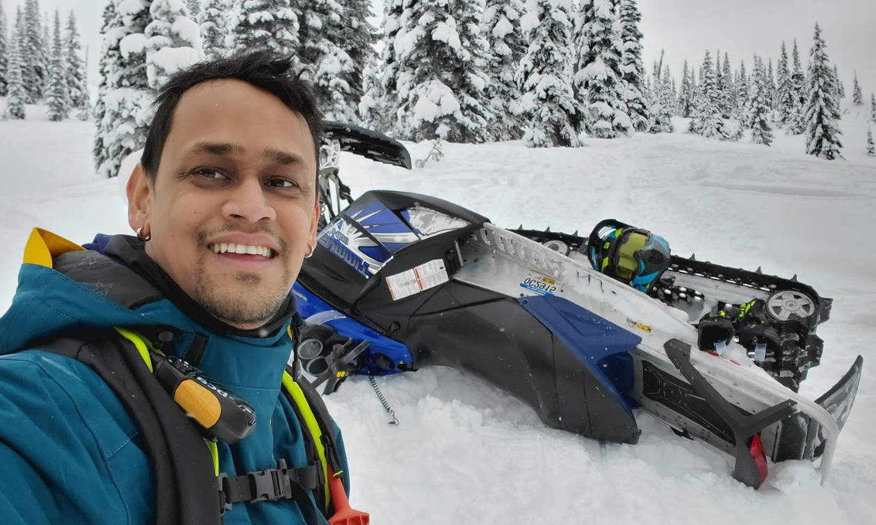 Melvin Garib smiles while his 2018 Polaris RZR S4 900 is parked on its side behind him.