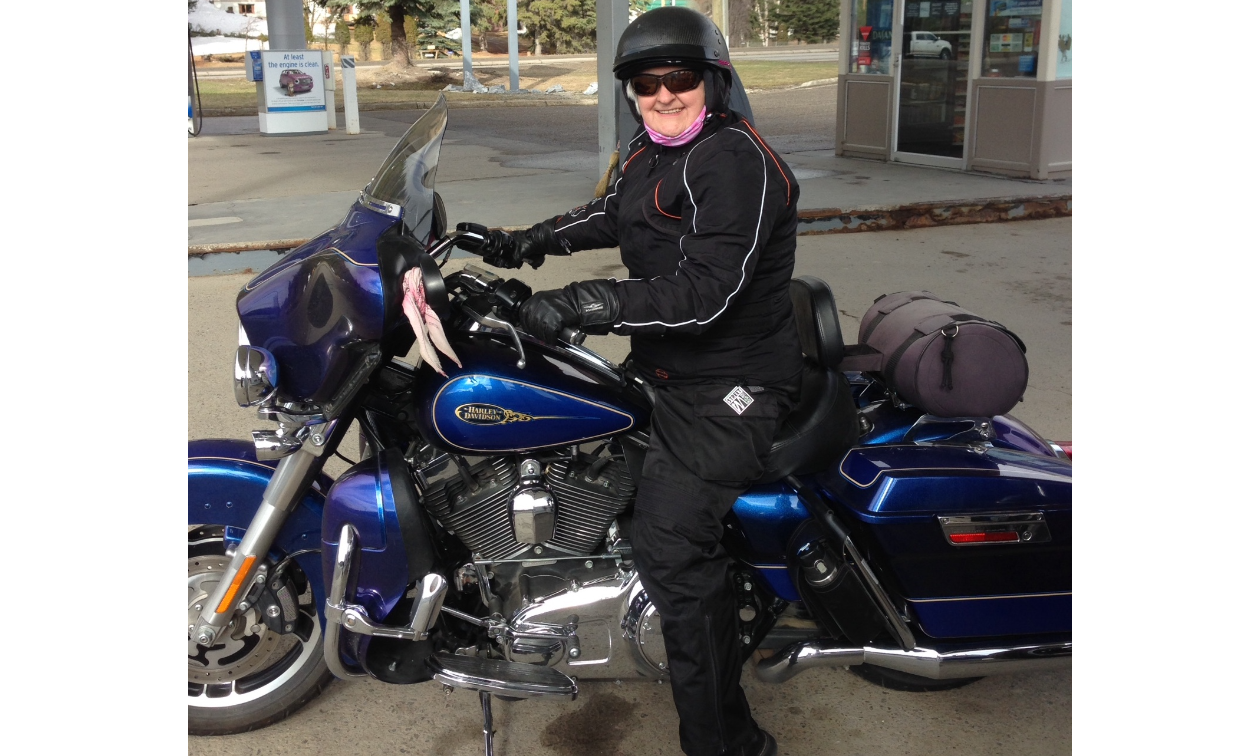 Nycole Ross rides a blue motorbike at a gas station.