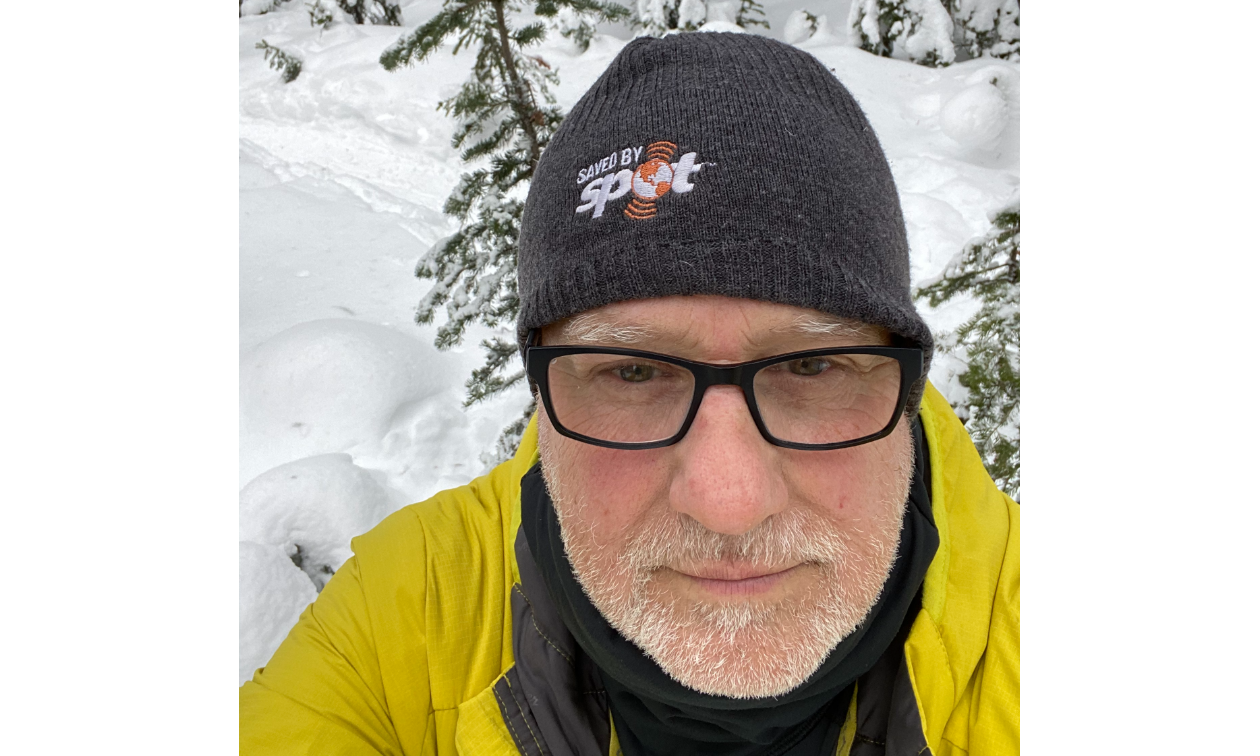 Randy Brown has a light, white beard and wears black-rimmed glasses and a grey toque that says SPOT.