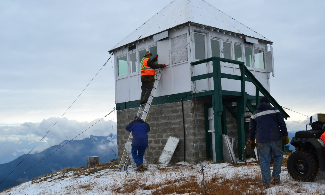 A group of people make repairs on the Sproat Mountain Fire Tower.