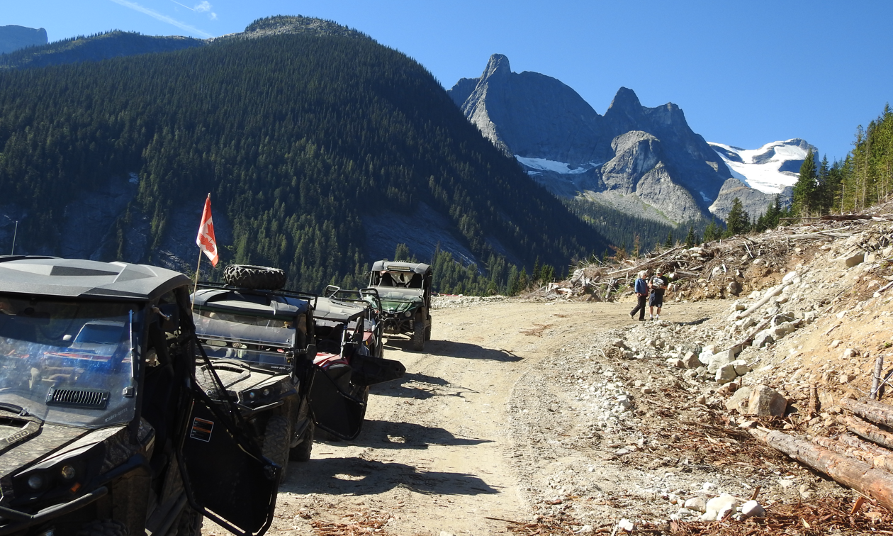 Huge green and grey mountainsides rise up in the distance. In the foreground, ATVs are parked on a trail.