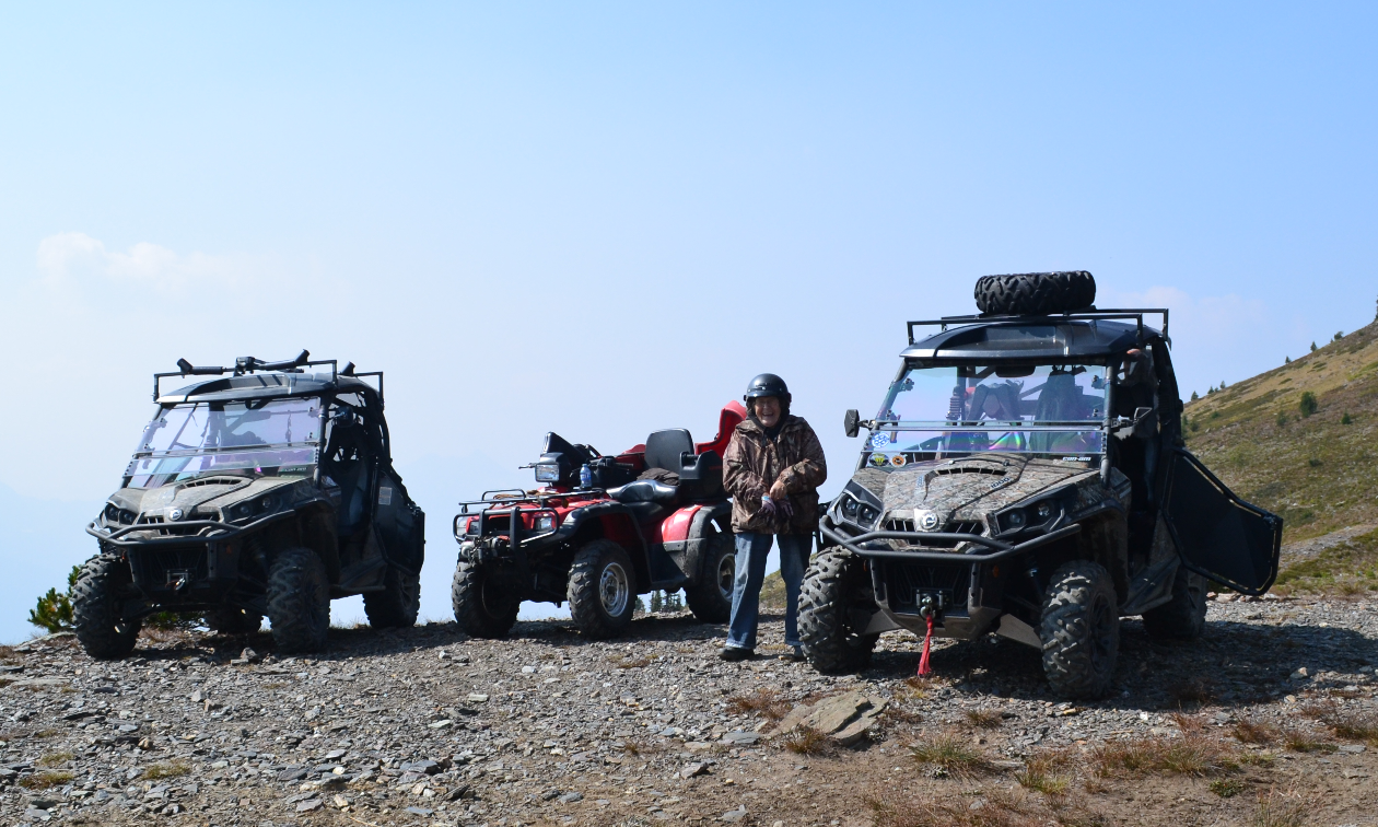 Three ATVs are parked on a gravel landing.
