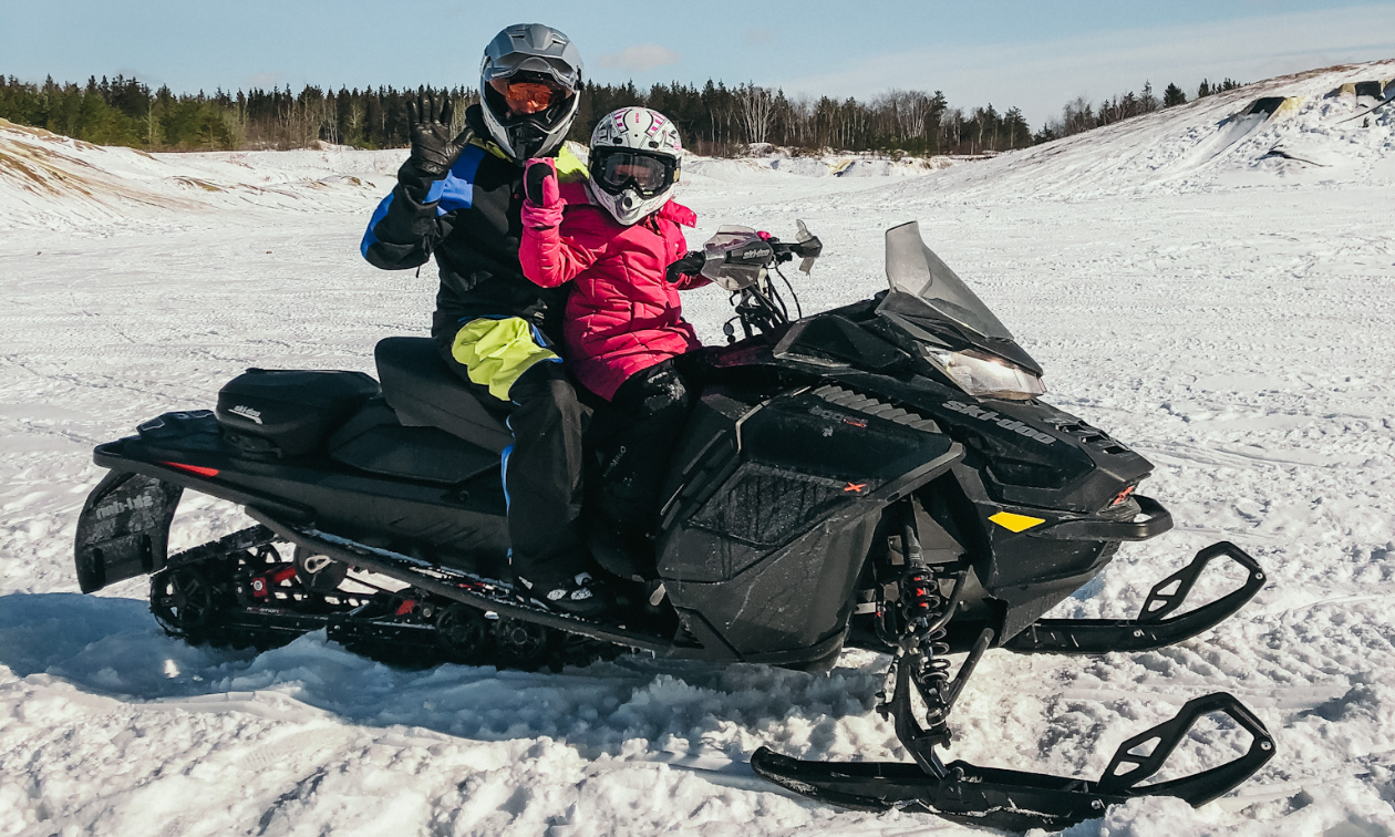 A man and little girl ride a black snowmobile on the plains in Manitoba.