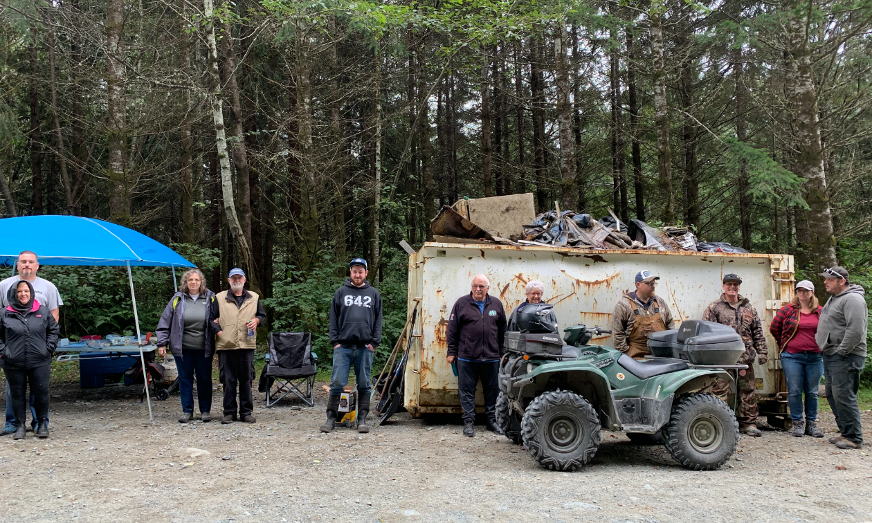 A group of ATVers gather around a dumpster full of garbage in the forest.