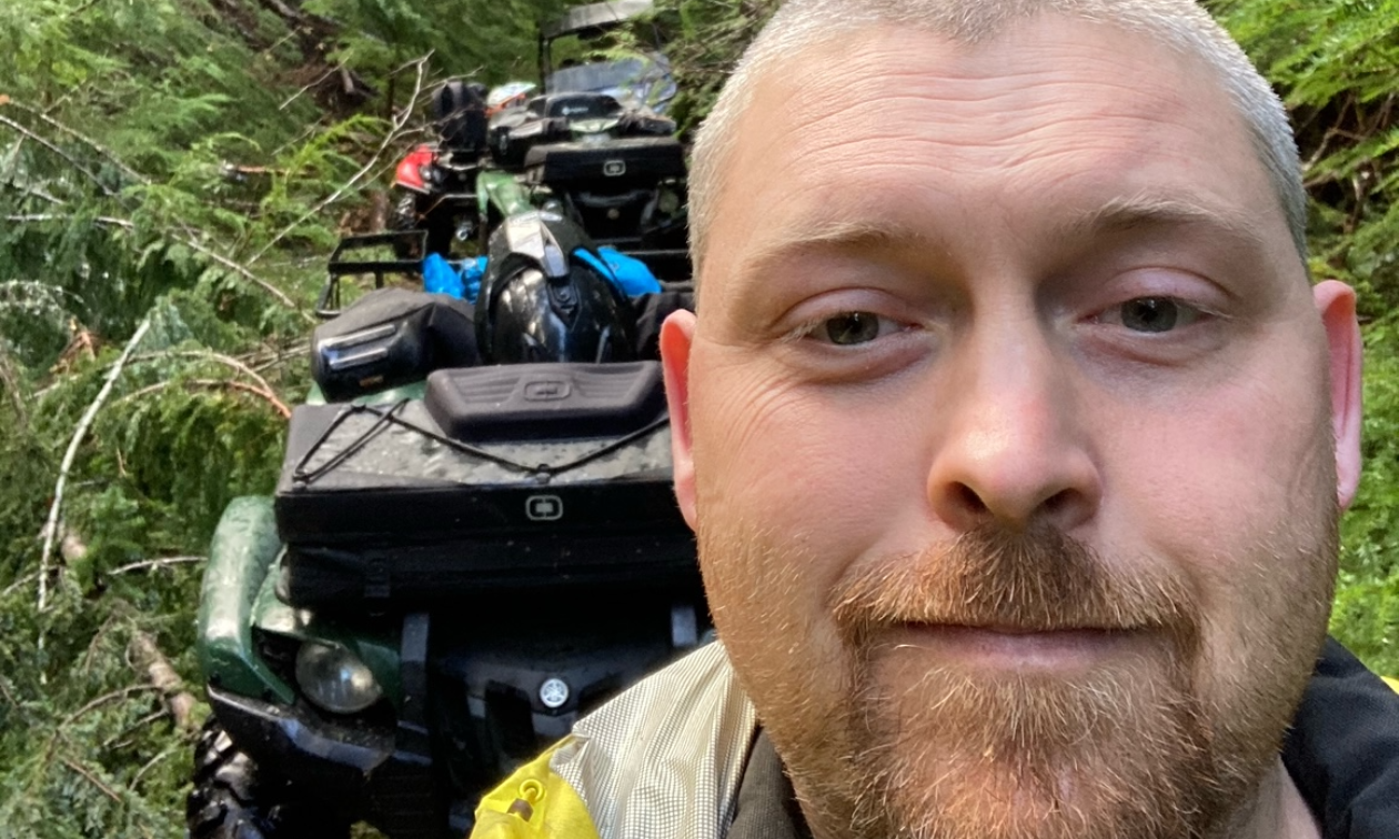 Dillon Baycroft has a shaved head and goatee and moustache. He is standing in front of a row of ATVs.