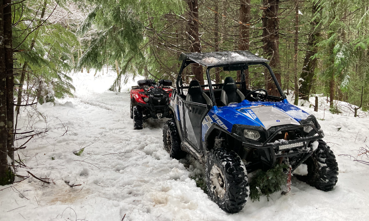 A blue side-by-side ATV is parked on a snowy trail between trees in the forest.