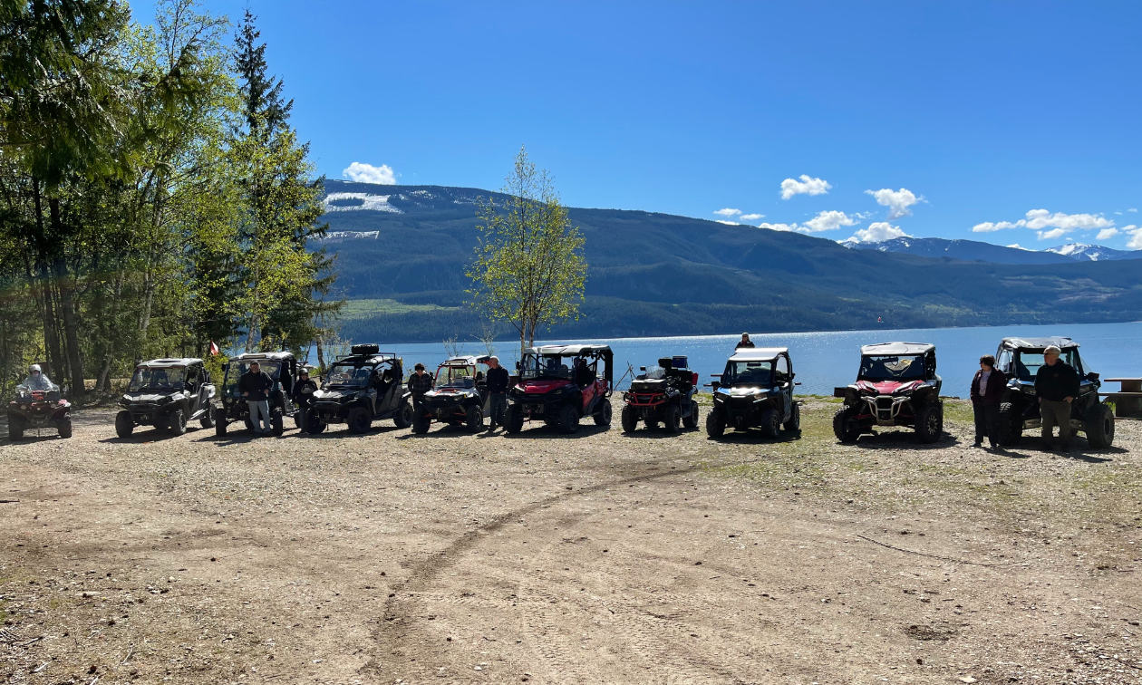 A row of ATVs lined up next to a lake in front of a mountain.