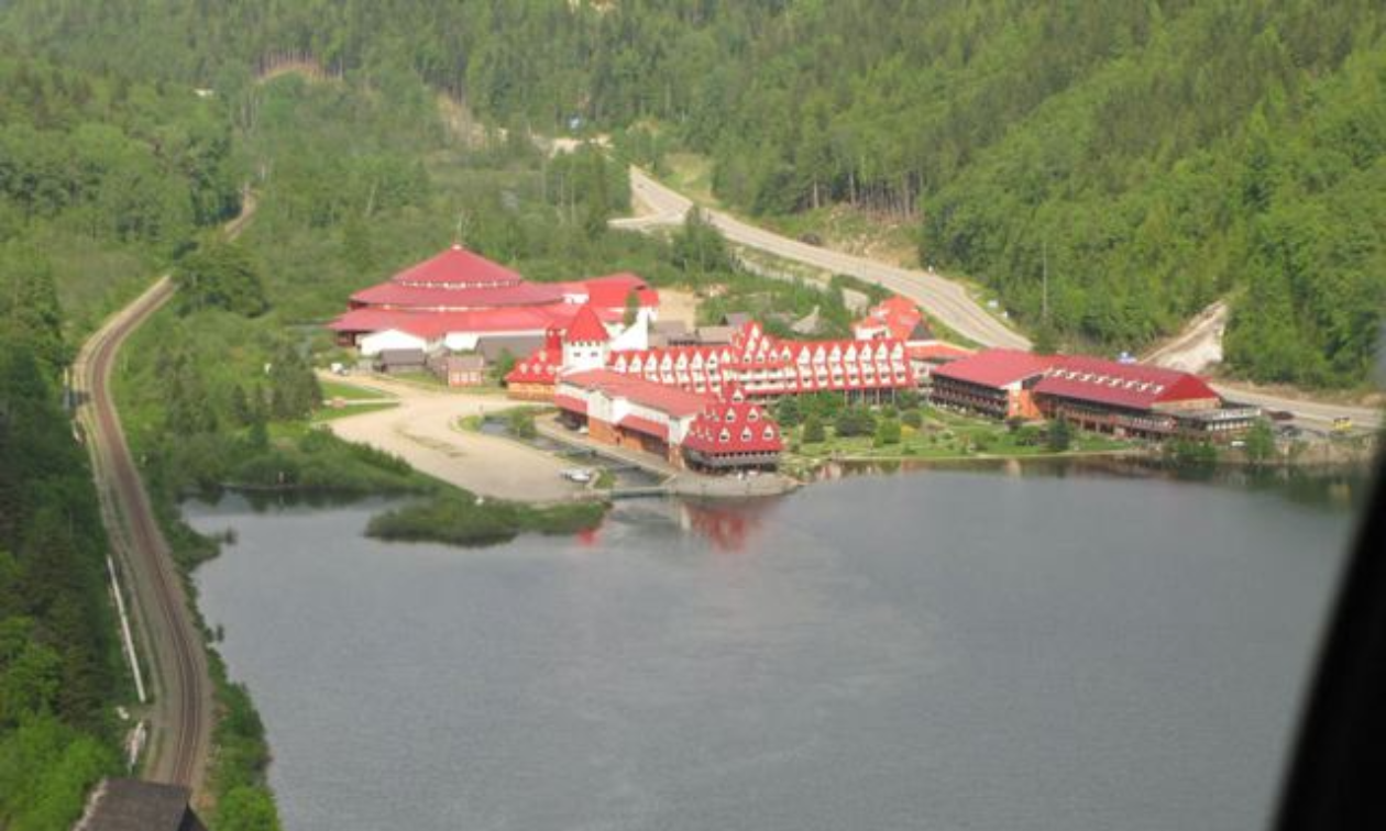 The Three Valley Gap resort has red roofs and is right on a lake.