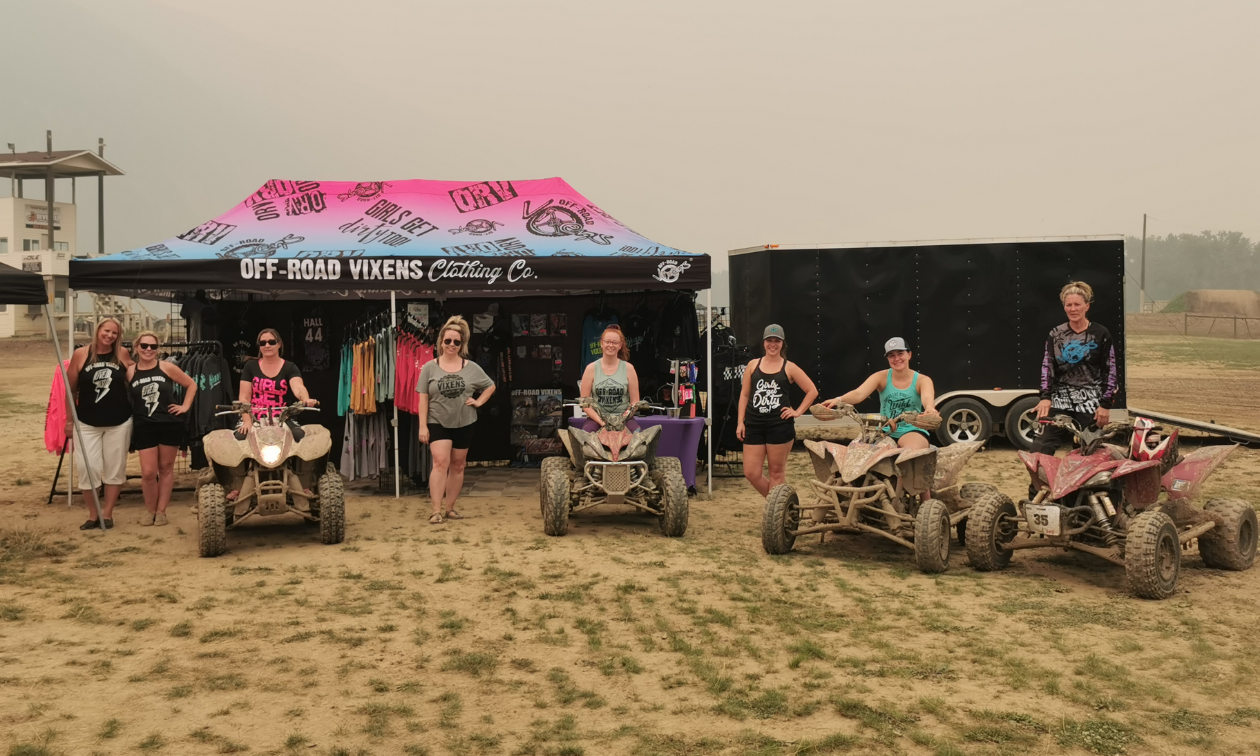 Four women stand on their ATVs in front of signage and a booth for Vixens Canada.
