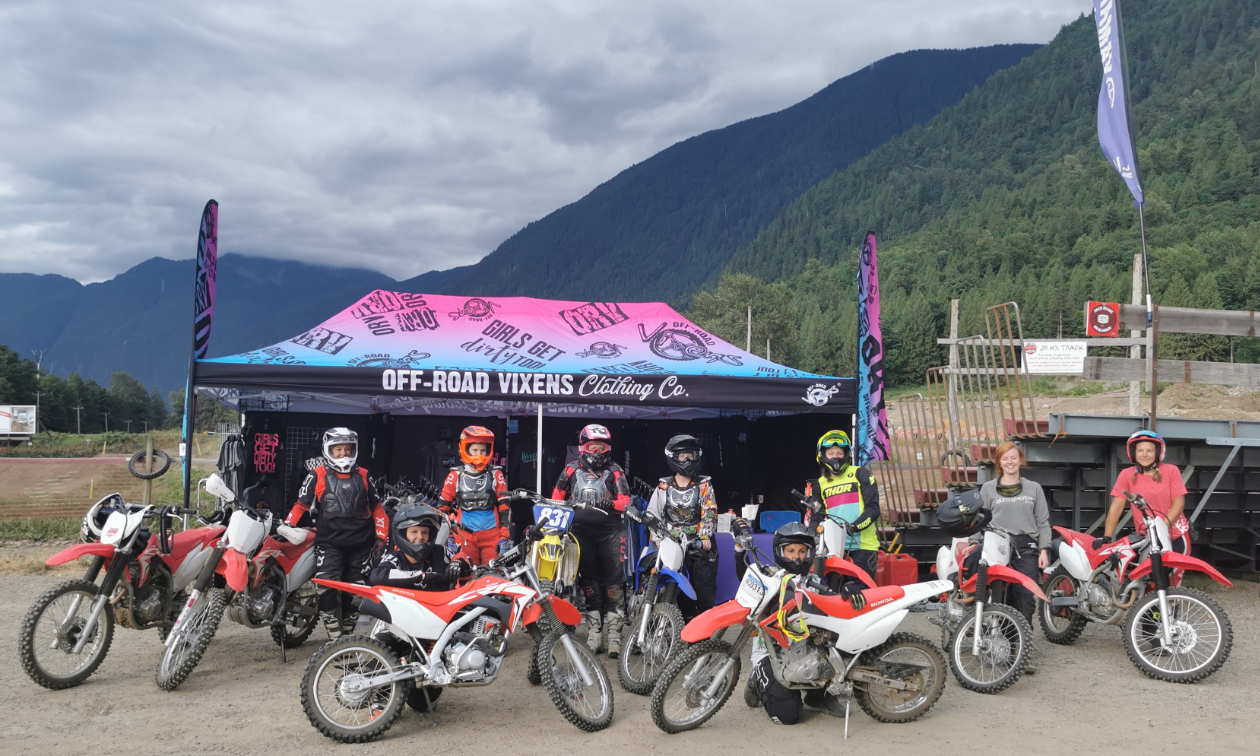 A group of female motocross riders pose in front of a Vixens Canada booth next to their dirt bikes.
