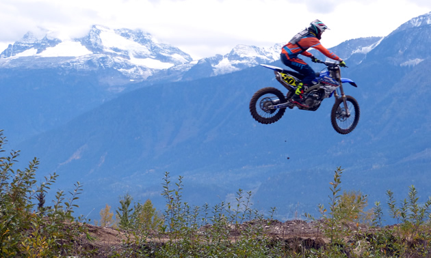 Dirt biker flying high in the air at the Revy Riders motocross track.