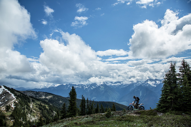Steve Shannon riding on the mountain with a blue sky dotted with fluffy white clouds in the background.