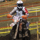 Photo of a girl riding around a dirt track on a bike.