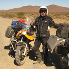 Photo of a guy in a black outfit and white helmet standing in the desert beside a black motorcycle and a yellow motorcycle.