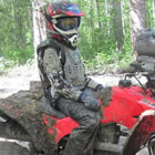 Photo of a young boy sitting on a red quad beside a large mud puddle.