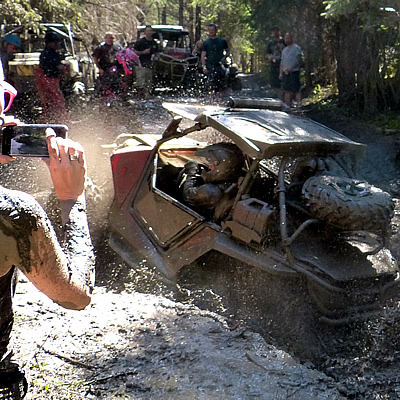 A SxS getting stuck in a giant puddle.