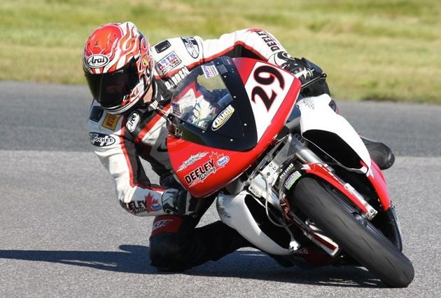 Darren James leaning over a sport bike in a road race.