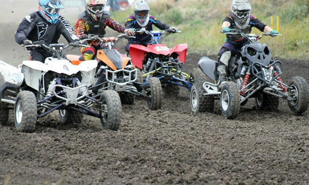 Photo of a guy in a black shirt and blue helmet racing an ATV.