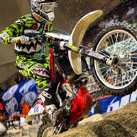 A man in a green racing jersey on a dirt bike.